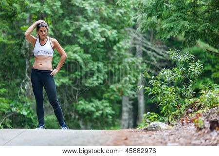 Middle Aged Woman Resting During A Run On Dirt Road