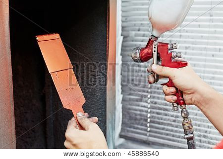 Hands of worker, who tries color for car painting, piece of metal in one hand and air-paint gun in another