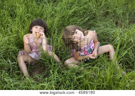 Two Girls Sitting In The Grass