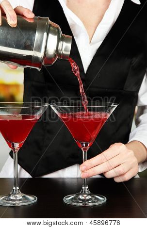 Barmen hand with shaker  pouring cocktail into glasses, on bright background
