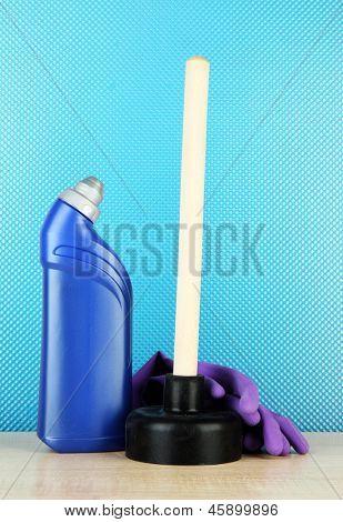WC Plunger, Handschuhe und saubere Flasche auf blauem Hintergrund