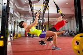 stock photo of gymnastics  - Crossfit fitness TRX training exercises at gym woman and man push - JPG