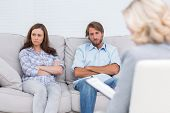 stock photo of psychologist  - Young couple going through therapy and listening to the therapist - JPG