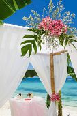 wedding arch and set up with flowers on tropical beach under palm trees