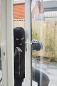 Burglar opening the terrace door with cro bar
