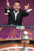 picture of roulette table  - Man throwing chips onto roulette table and smiling - JPG