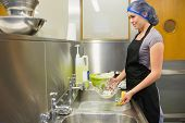 stock photo of untidiness  - Woman washing the dishes in the restaurant kitchen - JPG