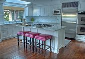 image of stool  - This is a beautiful modern kitchen with white cabinets walls and filled with light from windows and skylights - JPG