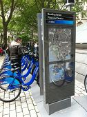 NEW YORK - MAY 24: A man looks at bicycles docked at a Citibike sharing kiosk at Bowling Green Stati