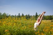 pic of ragweed  - Caucasian blonde woman stretching in yogo pose in the middle of a meadow of ragweed flowers - JPG