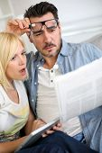 picture of horrifying  - Couple reading news with horrified look - JPG