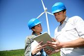 stock photo of turbines  - Engineers looking at wind turbine site with tablet - JPG