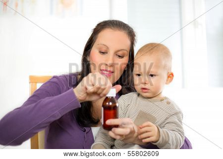 Mother giving medicine to baby