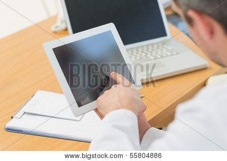 Extreme close-up of two doctors using laptop and digital tablet in meeting at the medical office