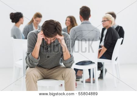 Group therapy in session sitting in a circle with therapist while man in foreground