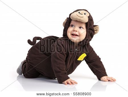 Baby boy in monkey costume looking up over white