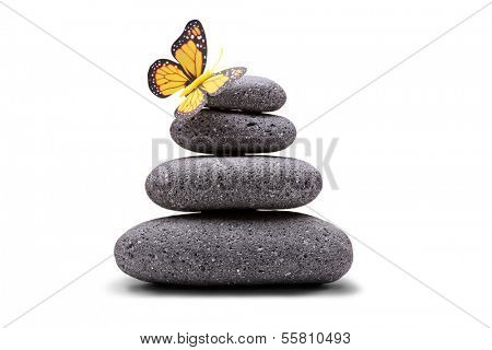 Butterfly on a stack of balanced stones isolated on white background