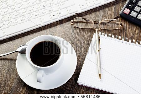 Business work place with cup of coffee calculator and glasses