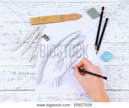 Hand draws a sketch with professional art materials, on wooden table