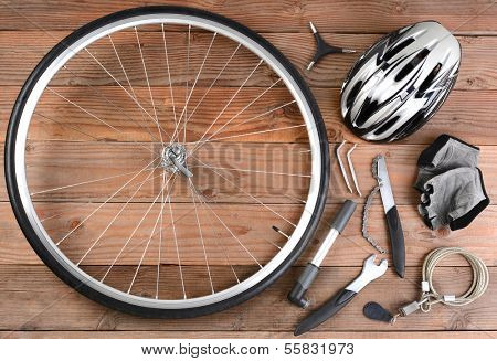 Overhead view of bicycle gear laid out on a rustic wooden floor. Items include, Wheel, pump, gloves, tools, helmet and lock. Horizontal format.