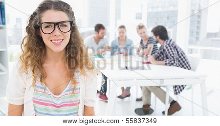 Portrait of a casual female artist with colleagues in the background at a bright office