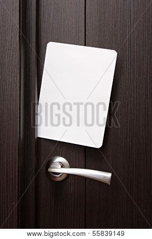 white envelope with message slipped under wooden door. Blank paper to write a nested in the gap unde