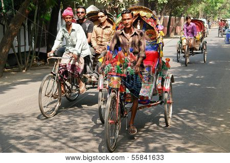 DHAKA, BANGLADESH - SEPTEMBER 17, 2009: Traditionally ornamented cycle rickshaws presents a very practical commute during rush hours of Dhaka traffic.