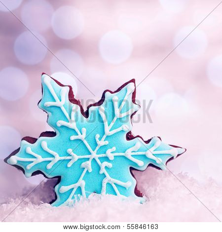 Tasty blue snowflake shaped cookie in snow decoration, traditional Christmas gingerbread, winter holidays dessert