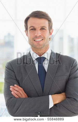 Portrait of a young businessman with arms crossed standing over blurred background outdoors