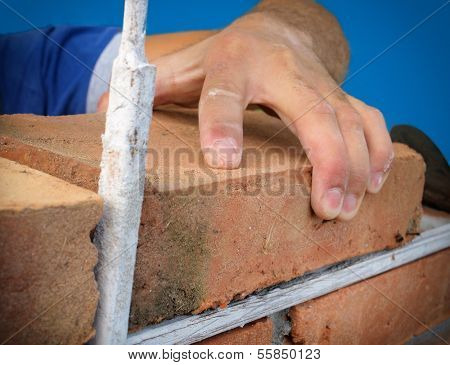 Close-up of construction process mason work with brick installation