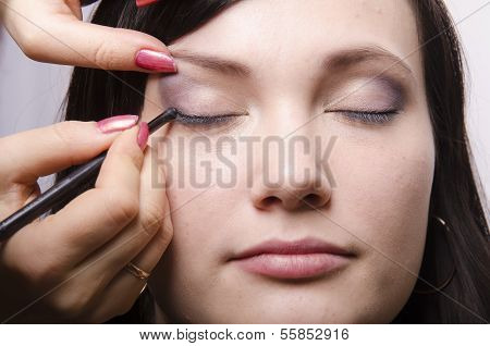Makeup artist in the process of makeup colors upper eyelids model
