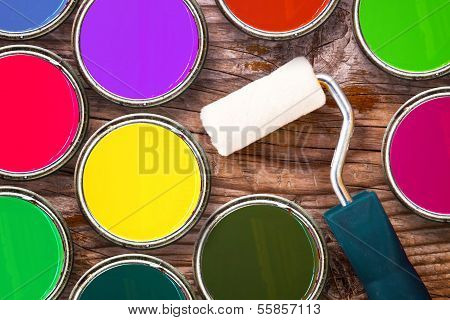 Paint Roller And Color Tin Cans Of Color On Wooden Background