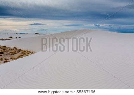 A Surreal View of a Large White Sand Dune with Cloudy Blue Skies and Desert Landscape in New Mexico