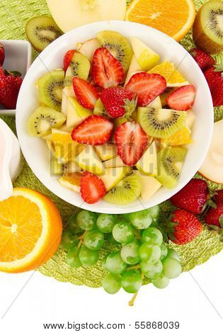 Useful fruit salad of fresh fruits and berries in bowl on napkin isolated on white