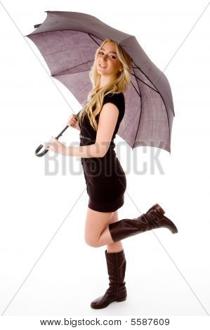 Side View Of Glamorous Model Carrying Umbrella