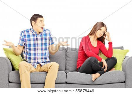 Young heterosexual couple sitting on a sofa during an argument isolated on white background