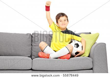 Happy boy in sportswear with a football sitting on a sofa and gesturing happiness isolated on white background