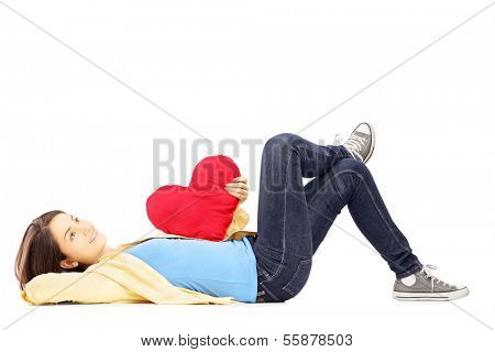 Smiling young female lying down with red heart in her hand isolated on white background