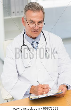Smiling doctor sitting at his desk writing on clipboard in his office at the hospital