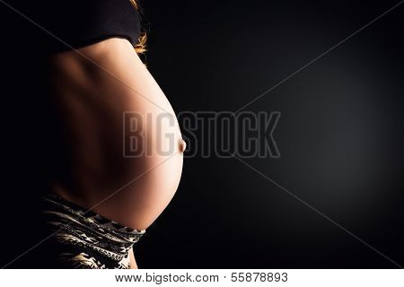 Close-up of a pregnant woman's tummy. Over black background.