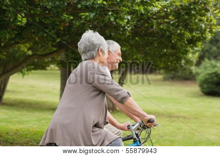 Side view of a senior couple on cycle ride in countryside