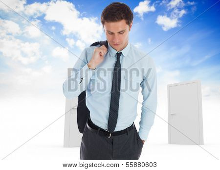 Serious businessman holding his jacket against closed doors in sky