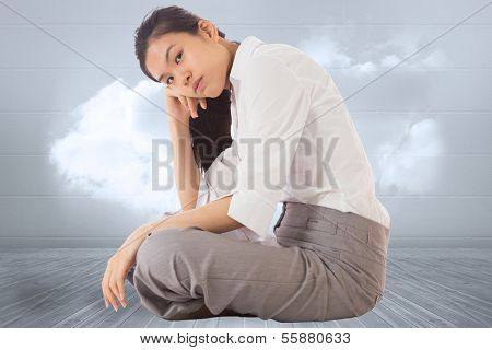 Businesswoman sitting cross legged leaning on hand against clouds in a room
