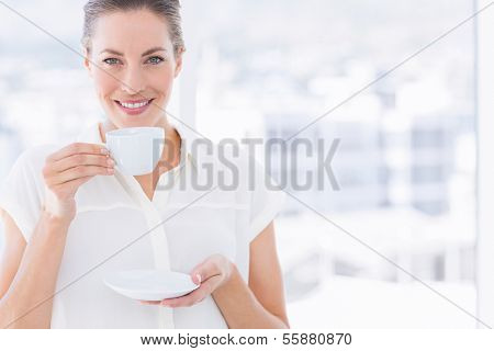 Portrait of a smiling young businesswoman with tea cup standing in a bright office