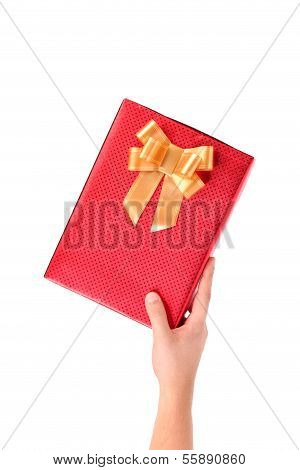 Hand holds red box with gold bow studded asterisks