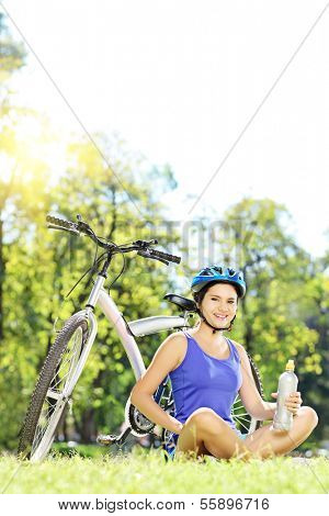 Young female biker with helmet sitting on a grass next to her mountain bike in a park, and relaxing on a sunny day