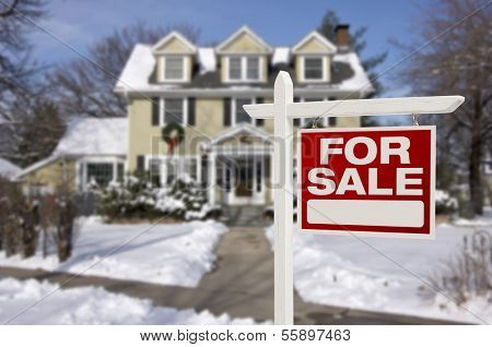 Home For Sale Real Estate Sign in Front of Beautiful New House in the Snow.