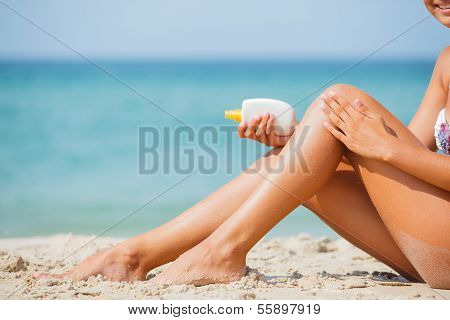 Beautiful young girl applying sunblock