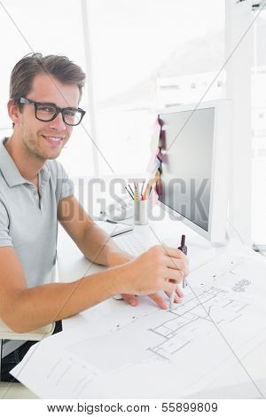 Side view of a smiling young man using compass on design
