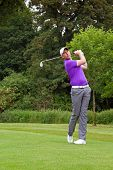 Photo of a golfer addressing the ball and playing a wedge shot into the green. Series of five in the